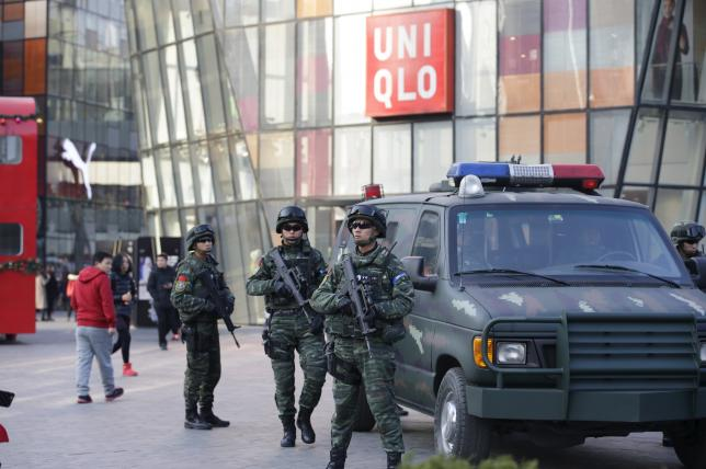 Armed policemen of the Snow Leopard Commando Unit (C) stand guard near a police van at the Sanlitun area, a fashionable location for shopping and dining, in Beijing, - Photo Jason Lee
