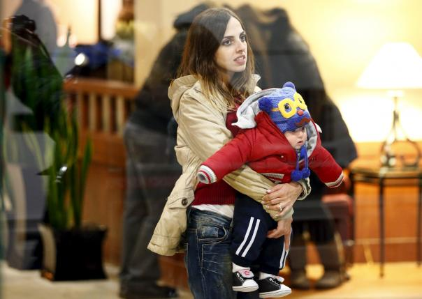 A Syrian refugee holds a child after arriving at a hotel in Mississauga, Ontario.