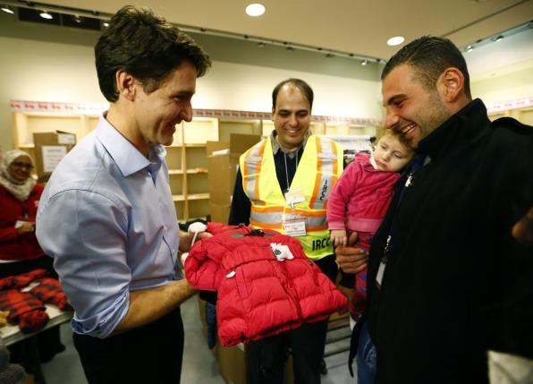 Syrian refugees are presented with a child's winter jacket by Canada's Prime Minister Justin Trudeau (L) on their arrival from Beirut at the Toronto Pearson International Airport in Mississauga, Ontario, Canada