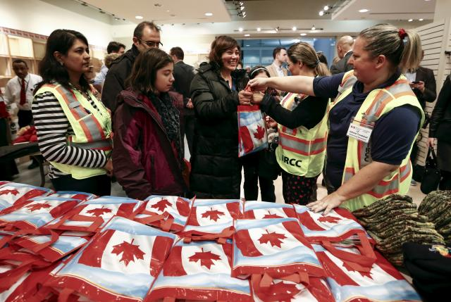 Syrian refugees receive welcome bags at the Toronto Pearson International Airport in Mississauga, Ontario, Canada