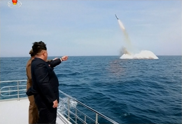 "Kim Jong Un, the ""Supreme Leader"" of North Korea, supervises the April 22 test-launch of a missile from a submerged platform."