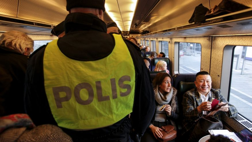 Swedish police officers perform identity control checks among the passengers aboard the train arriving in Malmo from Copenhagen