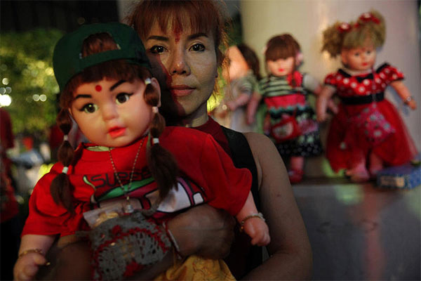 Coffee, tea or chucky: A woman lovingly embraces her Child's Angel doll