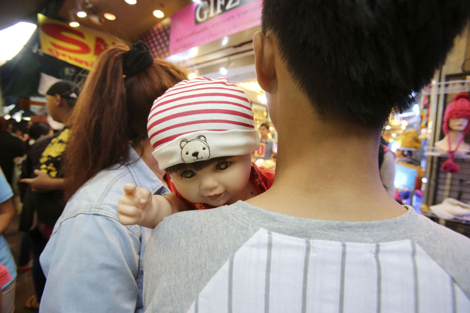 A Child Angel doll points over its owner's shoulder at a market in Bangkok.