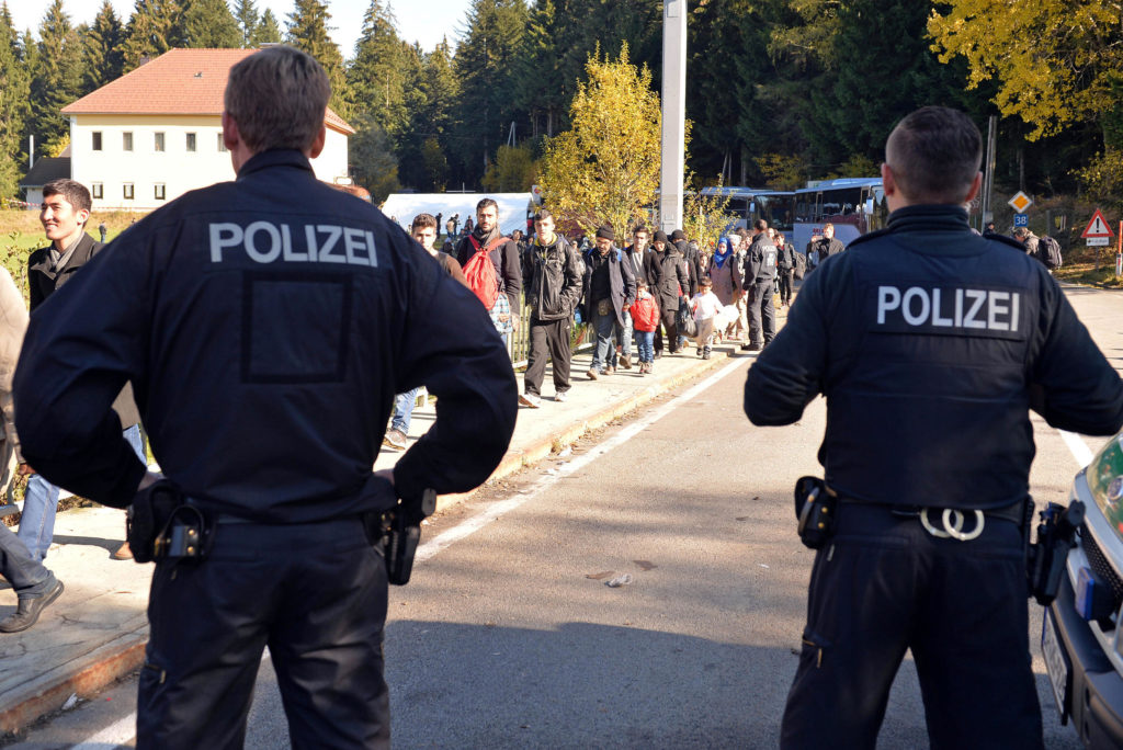 German police officers watch migrants crossing the border between Austria and Germany