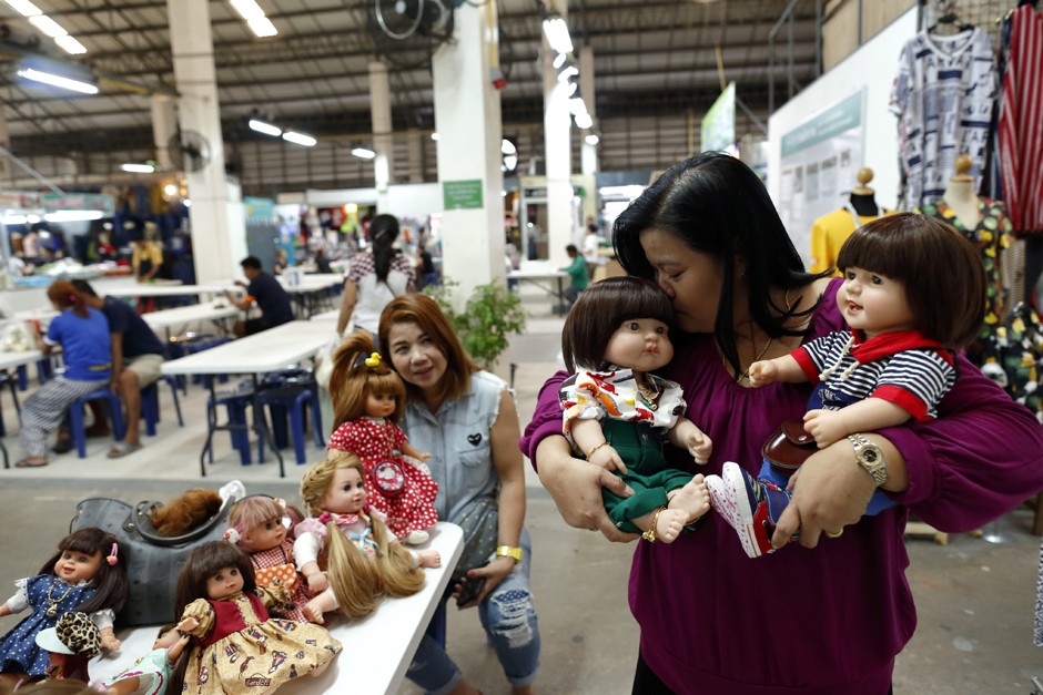 epa05124213 A picture made available on 25 January 2016 shows Thai devotees Ratchada Mahanavanont, 45, (R) kissing her Child Angels Dolls next to her friend Nita Kangvanchaivanich (L) as they get together at a market in Bangkok, Thailand,