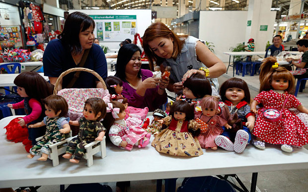 Ratchada Mahanavanont (C) talking to her friends Nipaporn Pornchaipimolpunt (L) and Nita Kangvanchaivanich (R), as they have together with their Child Angels dolls at a market in Bangkok
