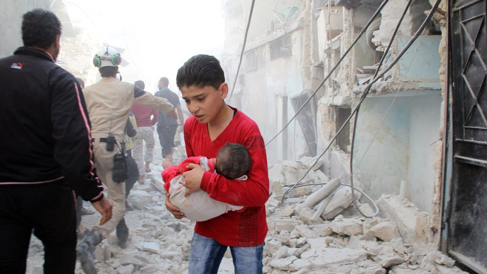 A Syrian boy carries Infant as he searches for his relatives in the rubble of destroyed houses following a Russian airstrike against the Syrian rebel stronghold of Aleppo.