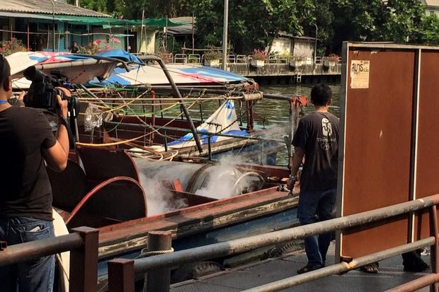 Police and officials inspect a taxi boat after its engine exploded, at the pier on Saturday