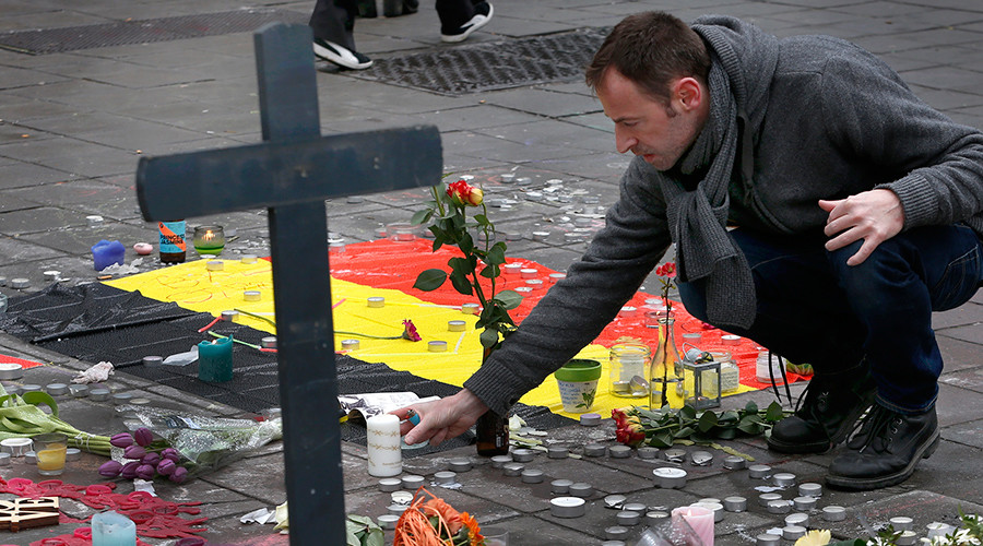 A man places flowers on a street memorial following Tuesday's bomb attacks in Brussels, Belgium
