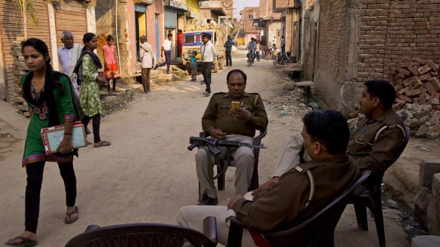 Policemen sit near a house where a 15-year-old girl was set on fire after being raped at Tigri village