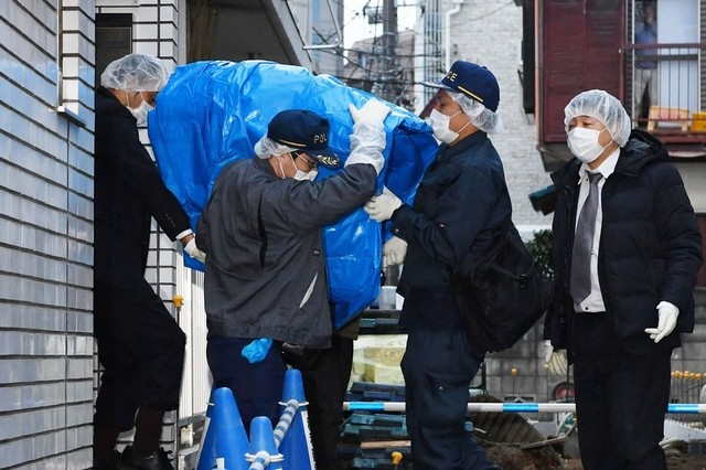 Police officers carry evidence from the apartment of Kabu Terauchi in Tokyo.
