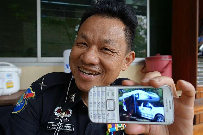 Thai tourist policeman Kitidesh Tajiwongsuriyakool with a photo of a campervan that was driven by a young Chinese couple travelling with their child through Chiang Mai last month