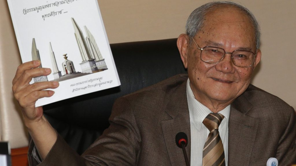 Chairman of the Constitution Drafting Commission Meechai Ruchupan holds the draft of new constitution during a press conference at the Parliament in Bangkok,
