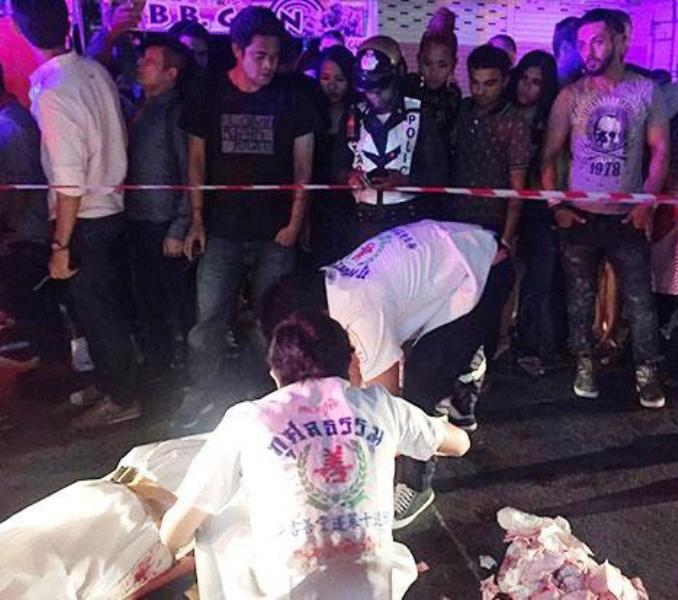 Rescue workers wrap the body of a French tourist who was stabbed to death at Patong beach in Phuket (Photo by Achadtaya Chuenniran)