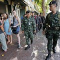 Military and police personnel walk past tourists as they patrol near the Grand Palace in Bangkok, Thailand