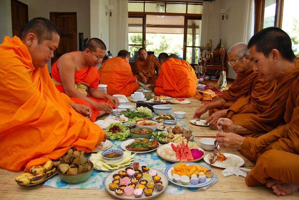 Thai monks eating at a house blessing , half the monks in Thailand are dangerously overweight