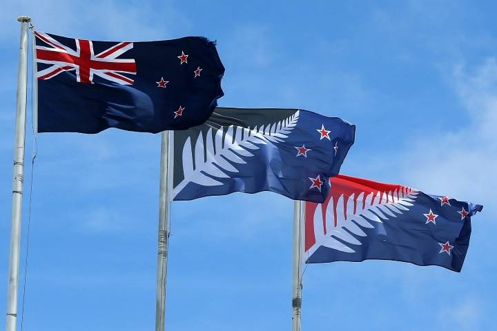 The current New Zealand flag (L) the referendum winning blue and black Kyle Lockwood designed flag (C) and the second placed red and blue flag (R) fly on a building in New Lynn, Auckland on December 14, 2015