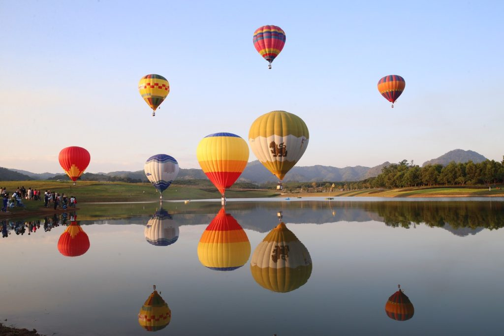 Balloons ascending into the sky over Singha Park's rolling hills and plantations