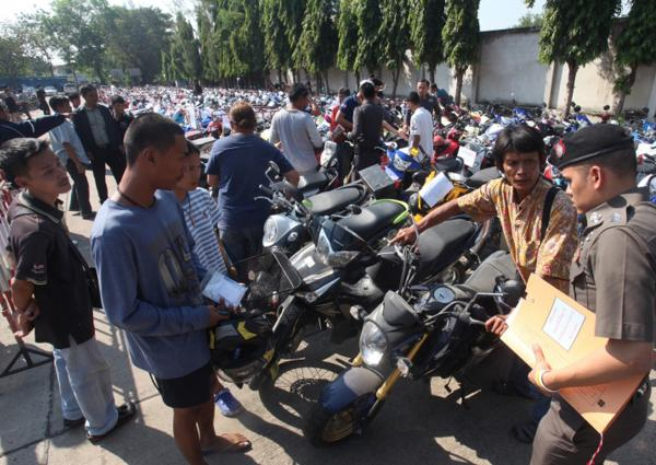 Police check the documents of people who showed up to reclaim vehicles that had been impounded