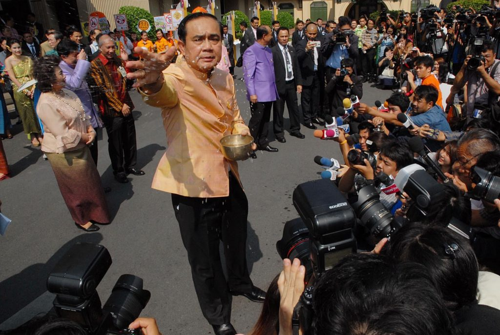 Prayuth Chan-ocha splashes water and greets the media to wish them prosperity and safety on Tuesday afternoon at Government House for the upcoming Songkran Festival