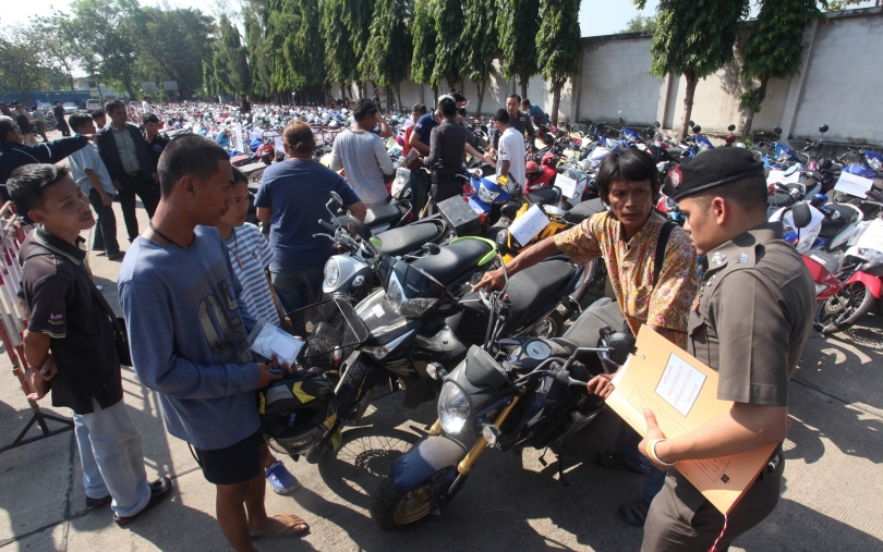 Police check the documents of people who showed up yesterday to reclaim vehicles that had been impounded for various reasons, including drink driving, at Boonyachinda Stadium in Bangkok.