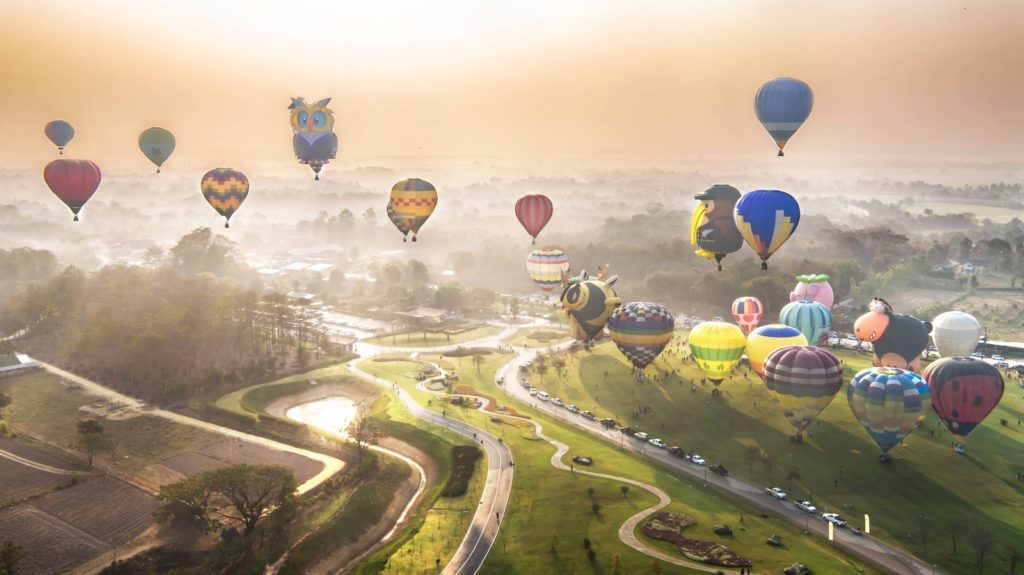 Balloons ascending into the sky over Singha Park's rolling hills and plantations. Photo by: Phudinan Singkhamfu