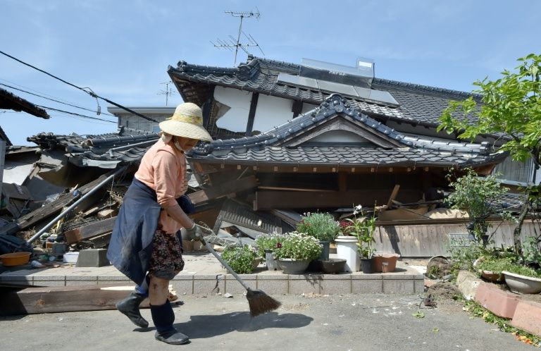 A woman cleans up in front of her collapsed house in the town of Mashiki,