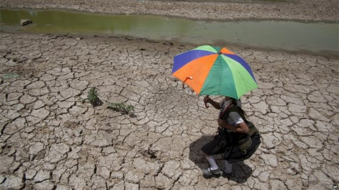 Young student walks alone dried up river bed in Northern Thailand
