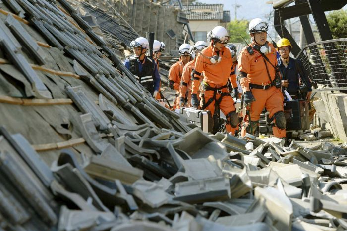 Firefighters walk among collapsed houses caused by an earthquake in Mashiki town
