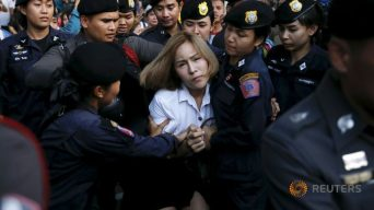 "A student activist is detained during a silent protest after Thailand's election commission filed charges against a group for posting ""foul and strong"" comments online criticising a military-backed draft constitution, in Bangkok"