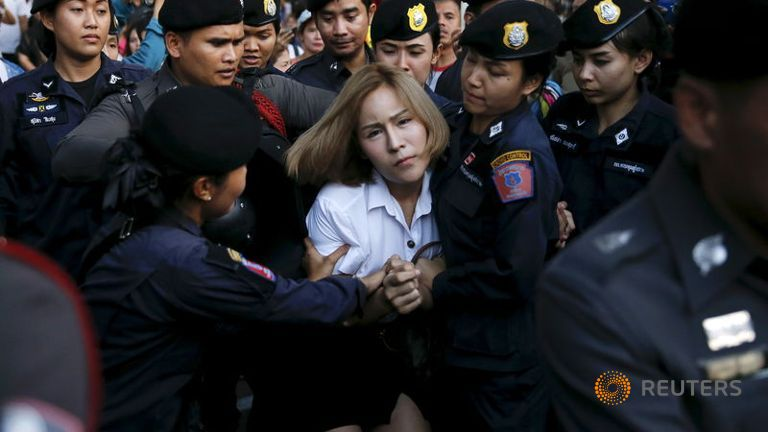 """A student activist is detained during a silent protest after Thailand's election commission filed charges against a group for posting """"foul and strong"""" comments online criticising a military-backed draft constitution, in Bangkok"""