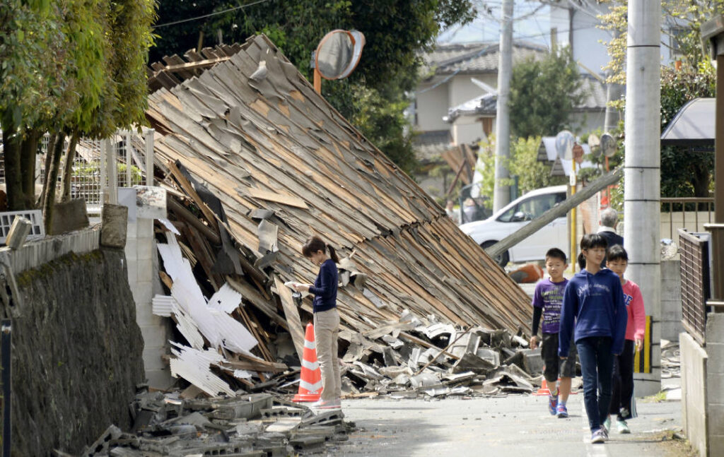 Children walk past a house collapsed by a magnitude-6.5 earthquake in Mashiki