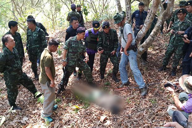 """Soldiers and police in Nan province stand over the body of a man believed to be Woenkhuan Sae Jao, 60, alias """"Saddam"""", a major drug trafficker in the area, who was killed in a gun battle with authorities that began Thursday afternoon. (Photo by Rarinthorn Petcharoen)"""