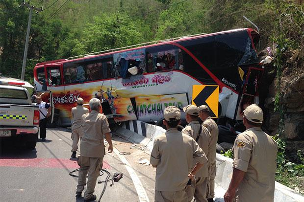 Rescue workers help injured passengers from the tour bus that crashed in a hillside at Tabtao curve in Si Sawat district of Kanchaburi province on Friday morning. The bus driver was killed and 22 passengers injured. (Photo by Piyarach Chongcharoen)