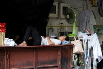 Restaurant workers sleep under a fan during a break in central Bangkok, where April's scorching weather has set a record for the longest heat wave in decades.