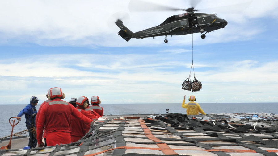 Sailors aboard the U.S. 7th Fleet command ship USS Blue Ridge stand by to move pallets