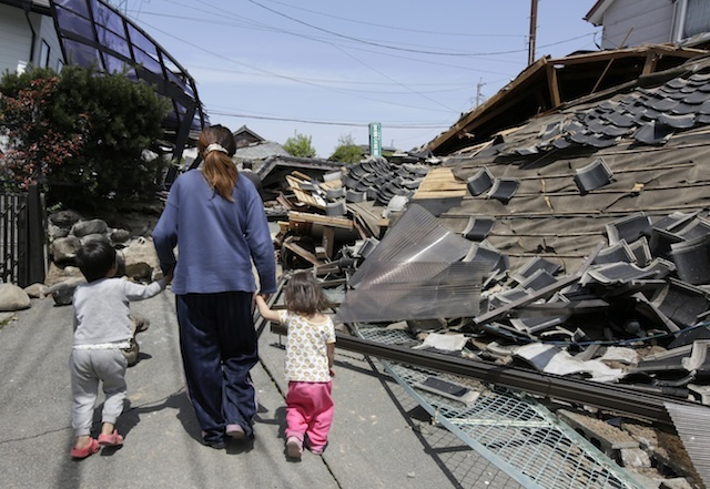 epa05259560  Residents walk through debris following a magnitude 6.5 earthquake in Mashiki town, Kumamoto