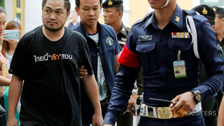 One of the nine people charged with sedition and computer crimes (black shirt) is escorted as he arrives at the military court in Bangkok.