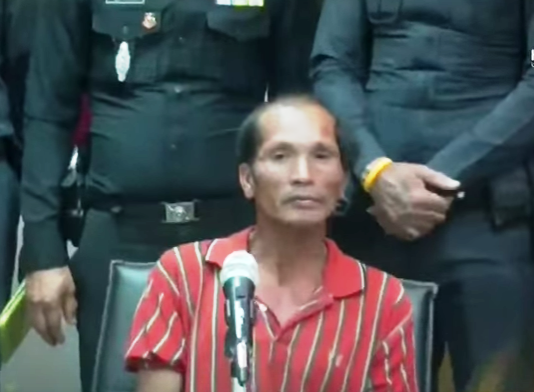 Sorn Humpiang, 45, (seated), is shown by police at a media briefing after being arrested for the murder and rape of a 14-year-old girl in Phitsanulok