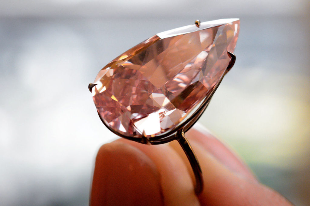 A model shows the 'Unique Pink' a rare and exceptional Fancy Vivid Pink diamond weighing 15.38 carats during a press preview by Sotheby's auction house on May 9, 2016 in Geneva. The Unique Pink will be offered at a 'Magnificent Jewels and Noble Jewels' auction in Geneva on May 17 with a pre-sale estimate of $28-38 million (CHF 27.2m  36.9m). / AFP / FABRICE COFFRINI        (Photo credit should read FABRICE COFFRINI/AFP/Getty Images)