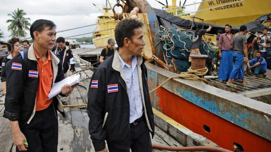 Thai officials inspect fishing boats docked at the compound of Pusaka Benjina Resources fishing company