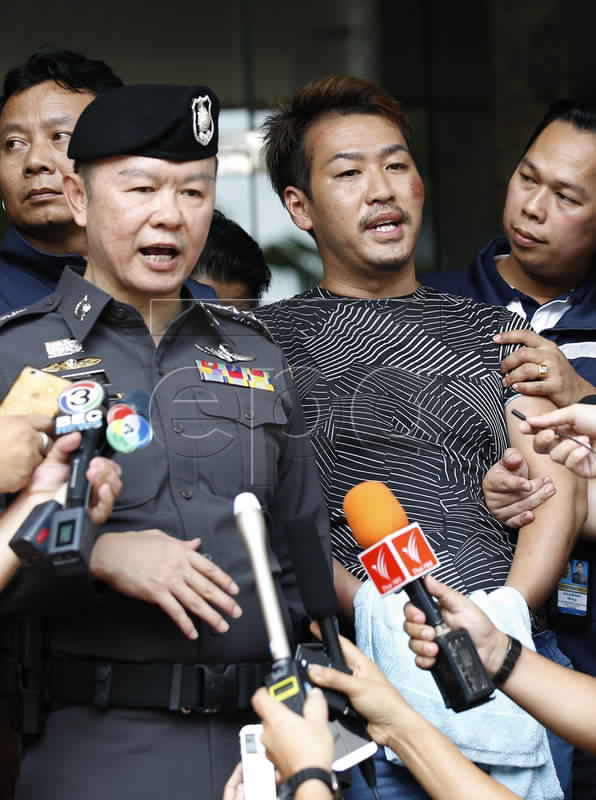 Alleged Yakuza member, Japanese Shuhei Yoshizawa is surrounded by Thai police officers during a press conference in Bangkok.