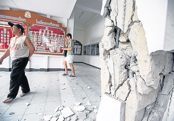 A man walks past a crumbling pillar after quake at Phan Phittayakom School in Phan district of Chiang