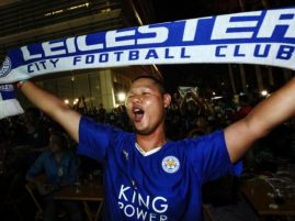 A Leicester City fan holds up a club scarf in Bangkok, Thailand