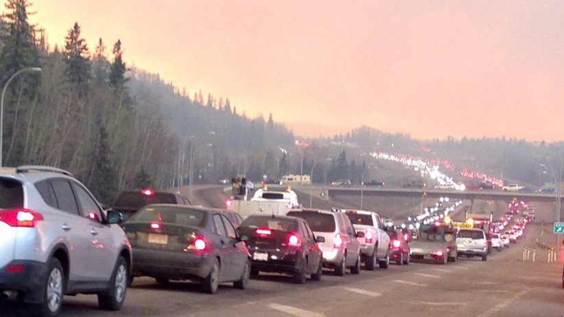Smoke fills the air as cars line up on a road in Fort McMurray, Alberta