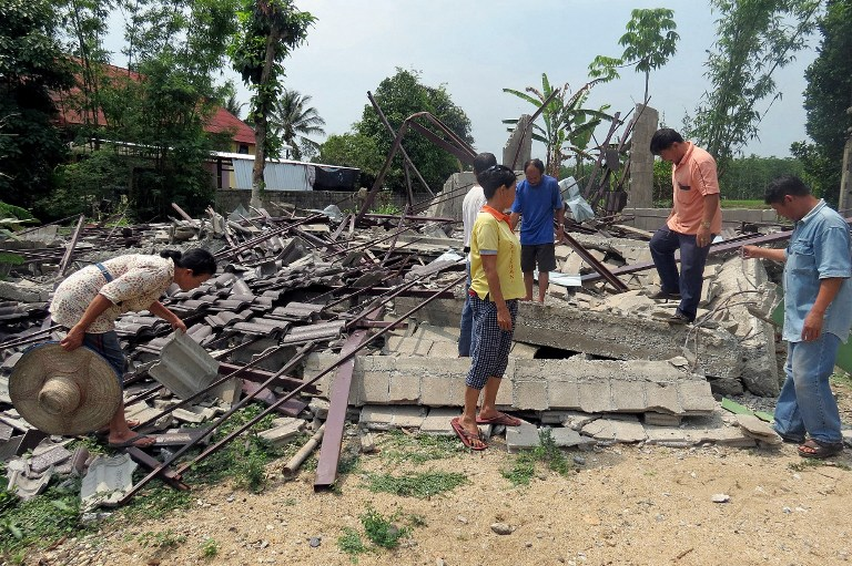 Engineer inspects a flattened building a day after a 6.0-magnitude quake struck in Thailand's northern province of Chiang Rai, on May 6, 2014.
