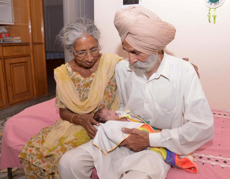 Indian parents Mohinder Singh Gill (R), 79, and Daljinder Kaur, 70, pose for a photograph as they hold their newborn baby boy Arman at their home
