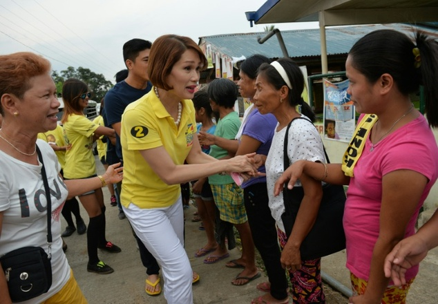 Legislator candidate Geraldine Roman (in yellow) shakes hands with voters during a campaign trip to the town of Orani, Bataan province, north of Manila