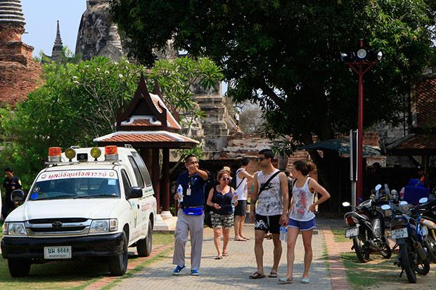 A plainclothes policeman talks to tourists at Ayutthaya Historical Park as safety measures are stepped following the assault and robbery of a German visitor